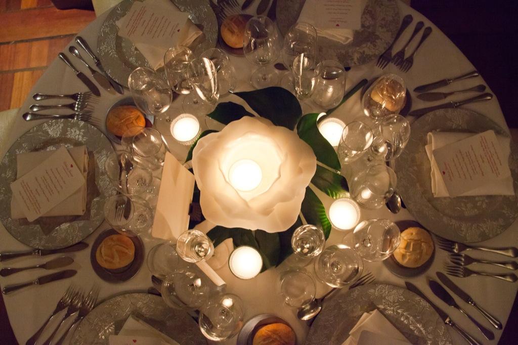 Decoraión de las mesas con velones en forma de rosa color blanco