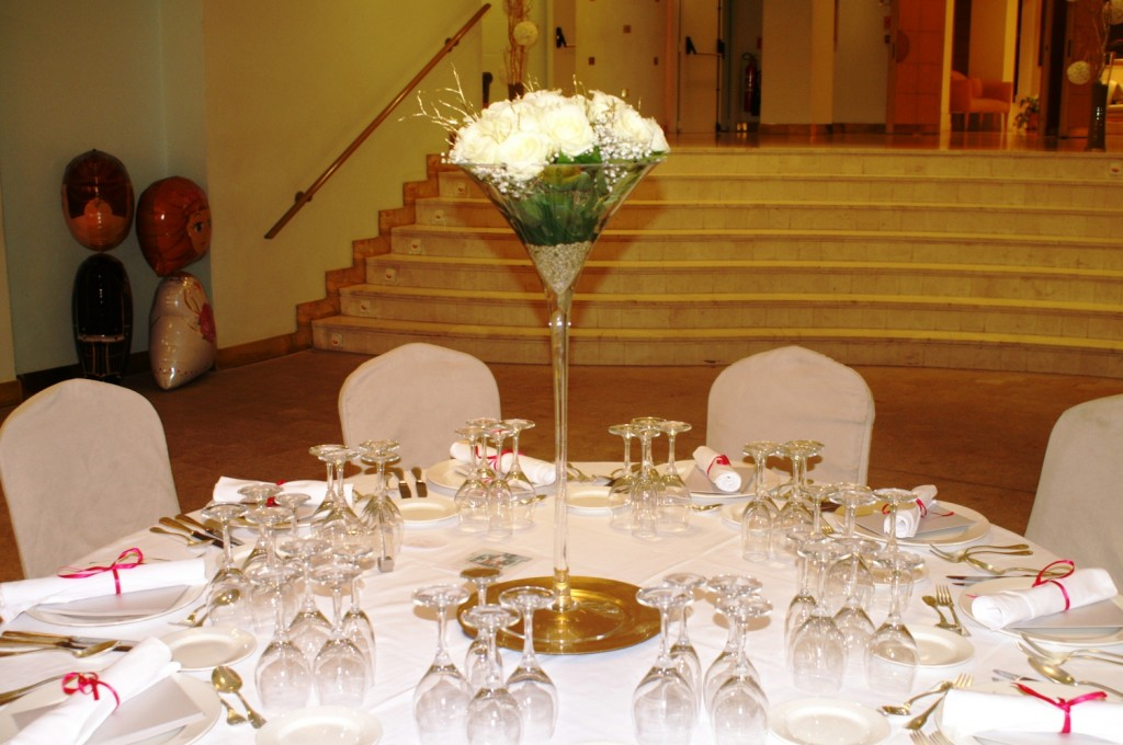 Centros en copa de Martini alta con rosas blancas y ramas doradas